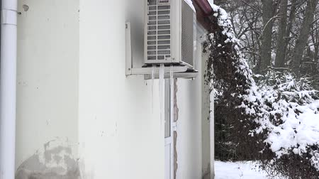refrigerant : Ice pile frozen under heat pump system on house wall in winter. Zoom in. 4K