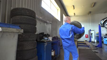 pneus : Stack of tires and male mechanic take one. Seasonal car tire changing in garage Vídeos