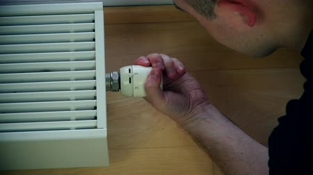grzejnik : Mans hand adjusting radiator temperature.