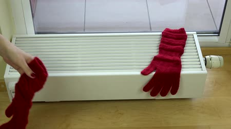 reheat : girl hand put red woolen gloves on radiator at home. Stock Footage