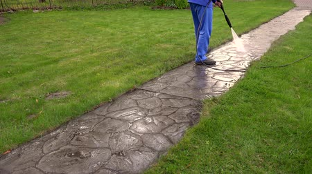 lavagem : Man Washing Concrete Path With Pressure Washer Vídeos