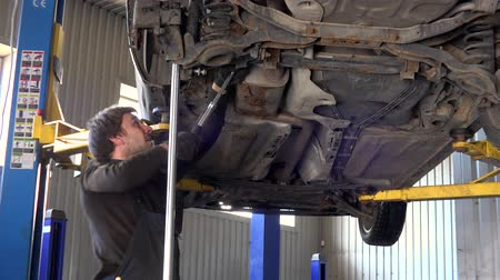 diagnostics : car mechanic with spanner tighten car of lifted automobile at repair service