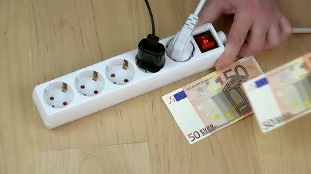 zástrčka : Man hand plugging device wires into electricity switch and money banknotes. Dostupné videozáznamy