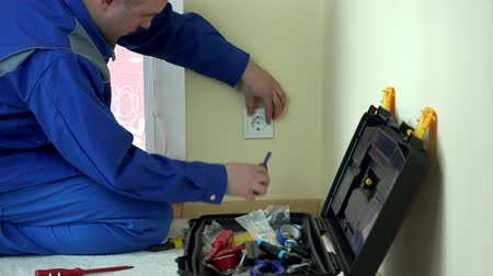 elektryk : Worker electrician repair an electrical outlet in apartment Wideo
