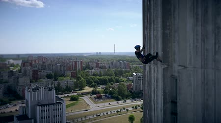 carabine : VILNIUS, LITHUANIA - JUNE 04, 2016: Athlete Alpinist man descend down on high skyscraper on background of city. 4K Stock Footage