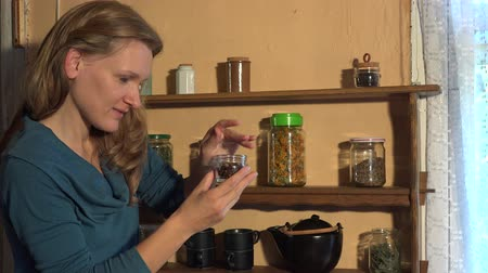 pot marigold : Country woman pour clove spices into small glass jar. 4K