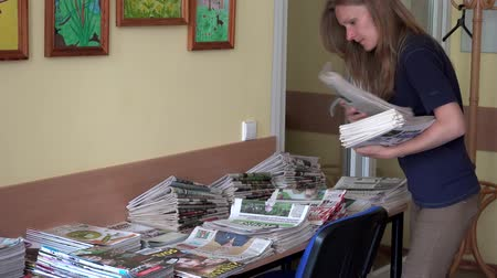 postacı : Female librarian girl sorting daily newspapers on table in library room.