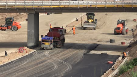 macadam : VILNIUS, LITHUANIA - AUGUST 19, 2016: Builders men team using heavy industrial equipment for road construction works. Building viaduct over highway. 4K