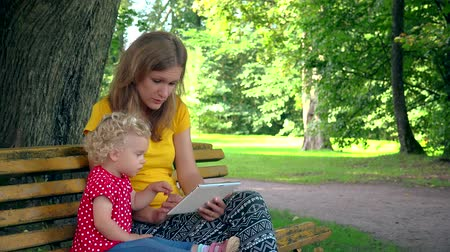 nanny holding : Mother with toddler daughter girl using tablet computer sit on bench in park
