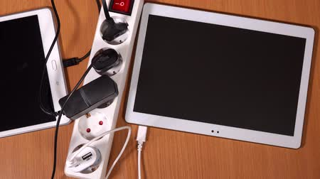 energized : Female hands plug tablet computers and phones to chargers in extension sockets Stock Footage