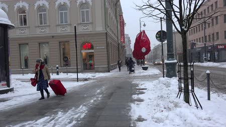 cityspace : VILNIUS, LITHUANIA - NOVEMBER 30, 2016: HM shop and people walking outside. Woman with red travel trunk on wheels. Blizzard snow falling. 4K