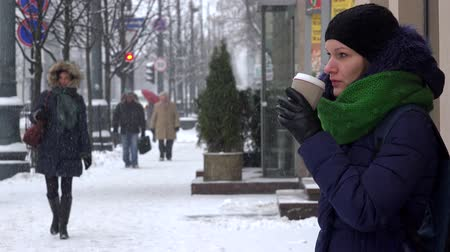 cityspace : VILNIUS, LITHUANIA - NOVEMBER 30, 2016: Woman drink cup of coffee tea hot drink in heavy snow blizzard and citizen passers by in winter city. 4K Stock Footage