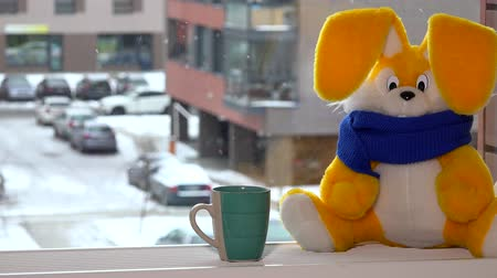 ülés : Yellow toy bunny with tea cup sitting by window in winter. Snowflakes falling.