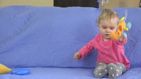 behemoth : Funny happy toddler girl playing with her toys on sofa.
