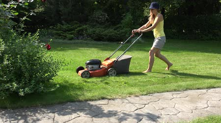 feminino : Young girl mowing green grass lawn with orange push mower. 4K Vídeos