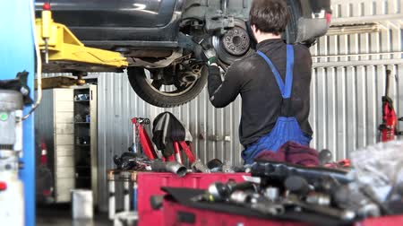 diagnostics : Service worker man change rusty car brake disk.