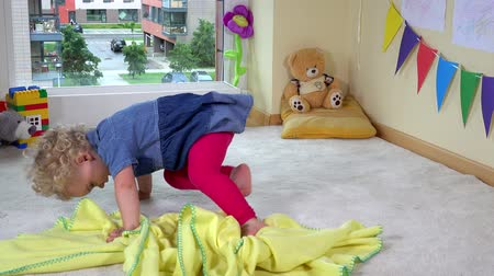cobertor : Mischievous toddler girl hide under yellow plaid blanket on floor