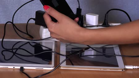 energized : hands plug devices charger to extension sockets on table