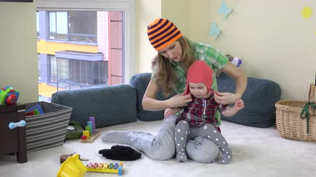 выросли : Mother with cute baby girl measure colorful knitted hats between toys