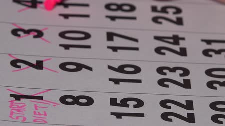 primeiro plano : Woman fingers with pink marker crossing days on calendar. Start of diet concept