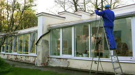 lavagem : professional male worker wash greenhouse roof and window