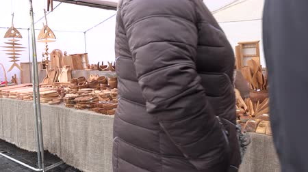 targi : VILNIUS, LITHUANIA - MARCH 04, 2017: Pretty woman and her man sell wooden kitchen utensil products in annual spring fair. Spoons and spatulas in kitchenware collection. steadicam flycam shot. 4K UHD