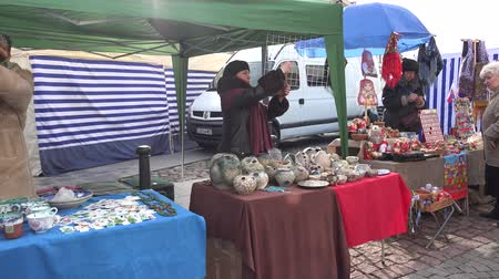 stragan : VILNIUS, LITHUANIA - MARCH 04, 2017: merchants sell handmade crockery goods in outdoor national spring fair event. Traditional crafts sale. Handheld steadicam flycam movement shot. 4K UHD Wideo