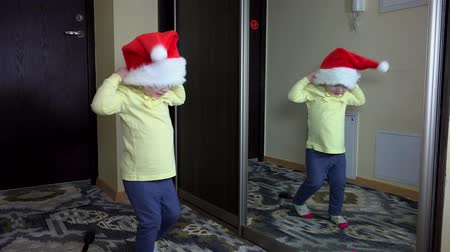 perverso : Funny girl put santa hat on head and jump in front of mirror. Careless childhood