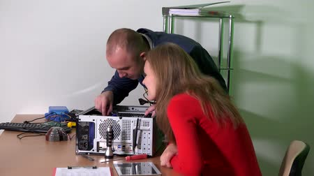 affairs : Man in suit help his colleague office girl to repair computer. woman flirting