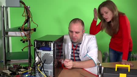 charlatan : Computer specialist man with stethoscope examining pc and customer woman