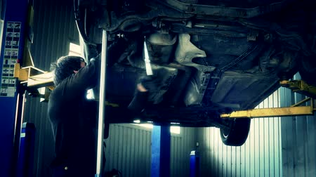 blockbuster : car mechanic with spanner tighten car suspension detail of lifted automobile
