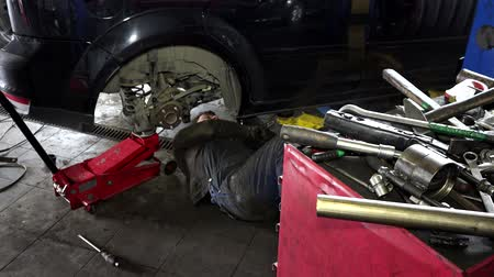 toolbox : Dirty man lying and working under car at repair garage