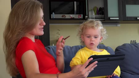 nanny holding : woman with little girl waving hands looking at tablet computer. Stock Footage