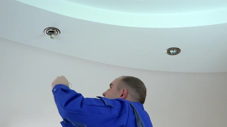 осмотр : electrician man install or replace halogen light lamp into ceiling