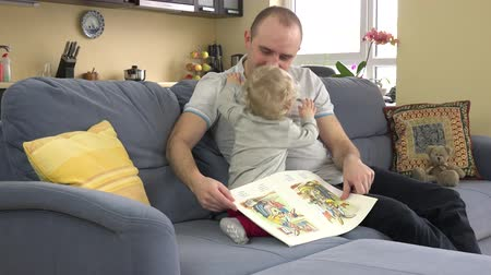 emotionally little girl read book with father on sofa room. 4K Stock Footage