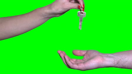 real estate female seller hand giving keys to male buyer on green