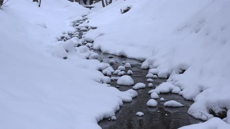 Snowy creek water flow in winter park channel. Snow fall. Zoom in. 4K
