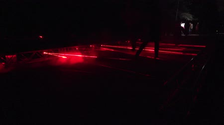 People walk laser formed red lines in park night light show. 4K