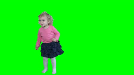 Adorable girl with blond curly hair dancing and jumping isolated on green