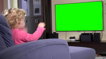 Adorable child looking at tv and dancing moving hands. Green chroma key screen