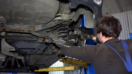 car mechanic with spanner tool strengthen brake system.