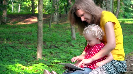 Babysitter woman with cute baby girl using tablet computer in park Stock Footage