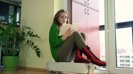 Pretty woman sit on home heater and read book in winter.