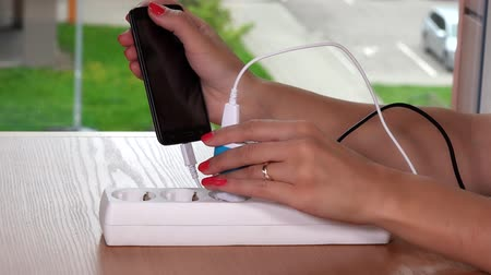 energized : hand plug charger cable in extension socket and hold charging phone