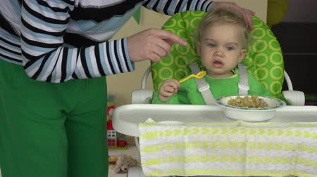 gruel : father learn baby girl eat gruel with spoon sit on highchair. 4K Stock Footage
