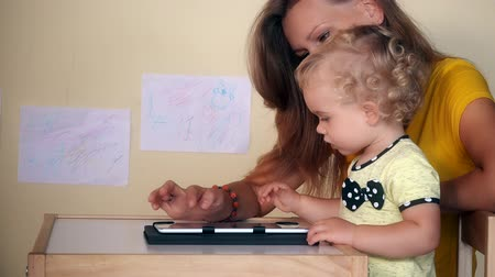 nanny holding : mother help her baby girl using tablet computer sitting at table.