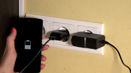 receptacle : female hand holding mobile phone plugged with wall charger