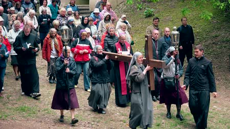 evangelical : Vestal sisters carry wooden cross. Calvary religious procession. Pentecost Stock Footage