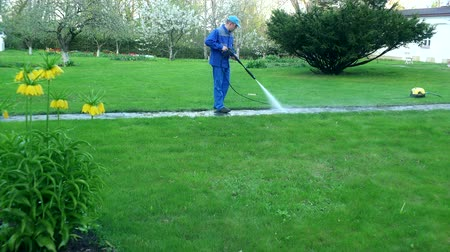 cleaning equipment : Gardener man washing footpath with high pressure water jet.