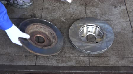 çinko : Mechanic hand put old worn brake disk and take new one.